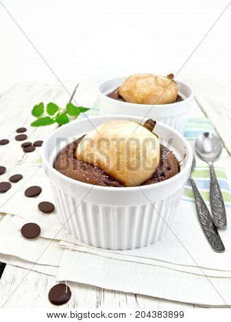 Two white bowl dessert with chocolate and pear, spoon, mint on a kitchen towel on the background light wooden boards
