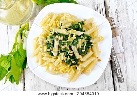 Penne pasta with spinach and cedar nuts in a plate on a napkin against a light wooden board on top
