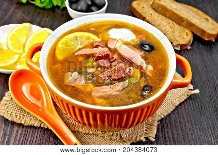 Soup saltwort with lemon, meat, pickles, tomato sauce olives in a bowl on a sacking, bread on a wooden board background