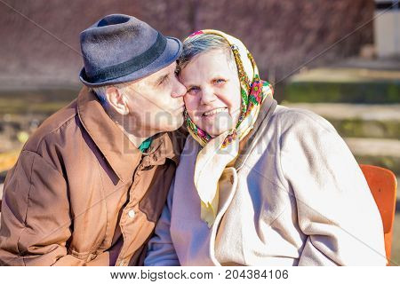 Happy elderly couple in love celebrating their anniversary. A happy and loving elderly man kisses his beloved wife on the cheek. Concept of happiness