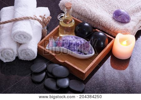 White towels connected by twine next to the set for massage from Bian stones, aromatic oil and purple salt, near the stones for a hot spa massage