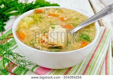 Soup fish kulesh with millet, potatoes and carrots and spoon in a bowl on a napkin, parsley, dill on a wooden board background