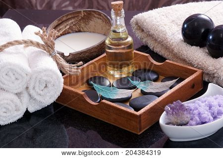 White towels knitted next to the set for massage from Bian stones, aroma oil and violet salt, in a wooden box a set of hot stones for relaxation and for a spa massage
