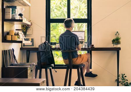 man in casual cloths sitting at coffee shop using his laptop computer and headphone vintage retor color tone good photo for modern and mobile digital lifestyle concept