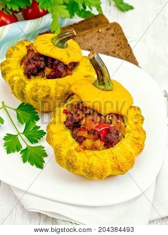 Two yellow squash stuffed with meat, tomatoes and peppers in the dish, bread, parsley and a napkin on the background light wooden boards