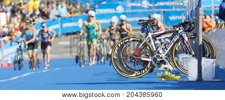 STOCKHOLM - AUG 26 2017: Parked cycles and female triathlete in the background in the transition zone in the Women's ITU World Triathlon series event August 26 2017 in Stockholm Sweden