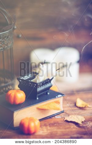 Background on the topic of Halloween and autumn: the black book, pumpkins, leaves, bats and burning wax candles on wooden background. Soft focus, toning