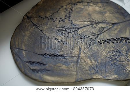 Dark brown dish made of clay, uneven shape with the imprint of grass and herbs . Technique of the drawing. Handmade