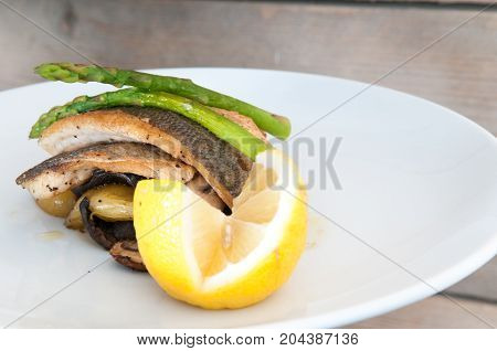 Gourmet Seafood Dish Of Fish And Asparagus On A White Plate