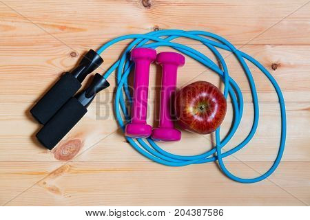 Dumbbells apple and skipping rope on wooden background. Top view