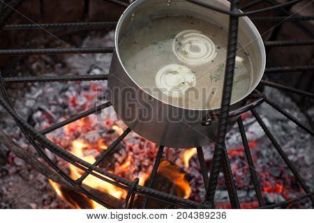 cooking broth in a saucepan and on the fire