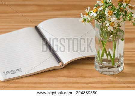 White notebook open on rustic wood table with brown or black pencil. Notebook open on desk with pencil and vase of camomile so freshness and relax.Copy space concept for background or wallpaper. Copy space for business or education concept.