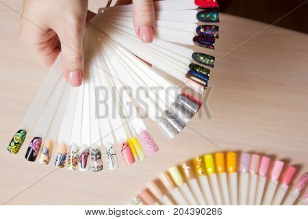 manicure and pedicure nail polish palette in a hand isolated on white background. cosmetic products