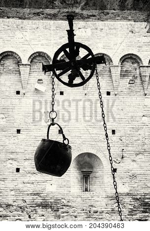 Metal bucket on a pulley hanging in the courtyard of the historic palace Siena Tuscany Italy. Black and white photo.