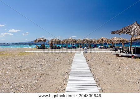Wooden path through sandy beach way to the tropical bar with sunshade and deckchairs.
