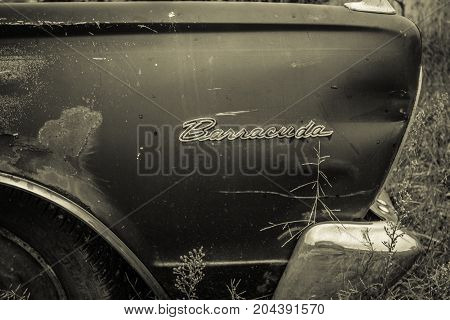 Croswell, Michigan, USA - August 24, 2017: Rusted front fender and logo of a 1966 Plymouth Barracuda rusting in a field.