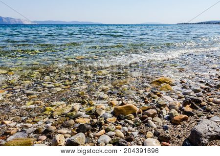Rocky seafloor visible through crystal clear turquoise transparent rippling water.
