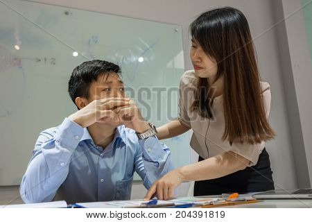Asian employee feeling annoyed when workmate ask to support