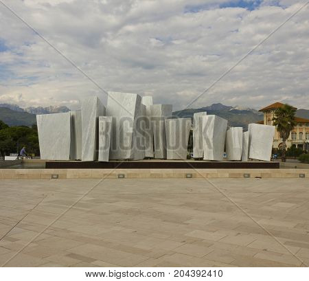 MARINA DI MASSA, ITALY - AUGUST 22 2015: Le Vele monument in white carrara marble in Marina di Massa Italy with the Apuan Alps in the background