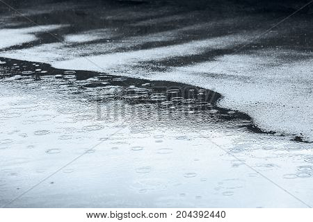 Raindrops Falling Into Water Puddle On Sidewalk