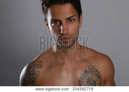 Sexy man posing shirtless on a gray background