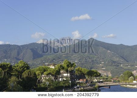 MARINA DI MASSA, ITALY - AUGUST 25 2015: View from the river front of Marina di Massa of the famous Tuscany Apuan Alps with the Carrara marble quarries