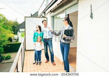 realtor showing a family of three the view they would enjoy on their balcony