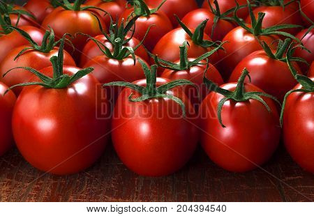 Bunch of fresh tomatoes on old wooden table dark lighting
