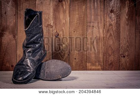 Old leather boots on dirt wooden background