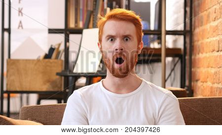 Portrait Of Amazed Red Hair Young Man, Loft Office