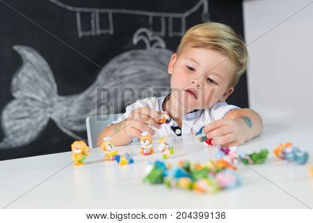 Portrait of cute toddler boy playing with toys at the desk at home. Children learning.