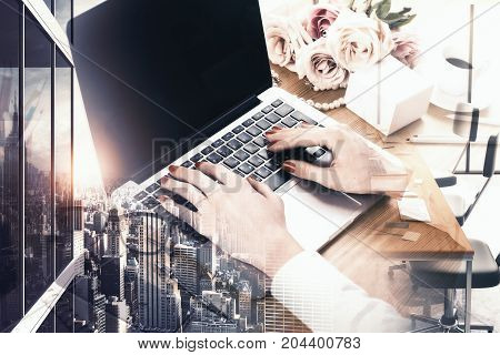 Side view of woman hands using laptop with empty screen placed on wooden girly desktop. City background. Mock up Double exposure