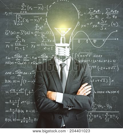 Light bulb headed businessman with folded arms standing on chalkboard wall background with mathematical formulas. Solution concept