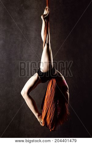 Beautiful sexy dancer on aerial silk, graceful contortion, acrobat performs a trick on a ribbons.