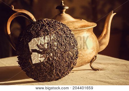 Teakettle with Pu-erh tea in shape of cake traditional chinese drink. Popular antioxidant tea from China at kitchen table
