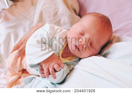 Mother holding her newborn baby child after labor in a hospital. Mother giving birth to a baby. Parent and infant first moments of bonding.