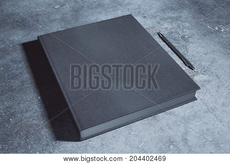 Empty black hardcover notepad and pen placed on concrete desk. Supplies stationery items paperwork concept. Mock up 3D Rendering