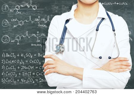 Female doctor with folded arms standing on chalkboard background with chemical formulas. Medicine and chemistry concept