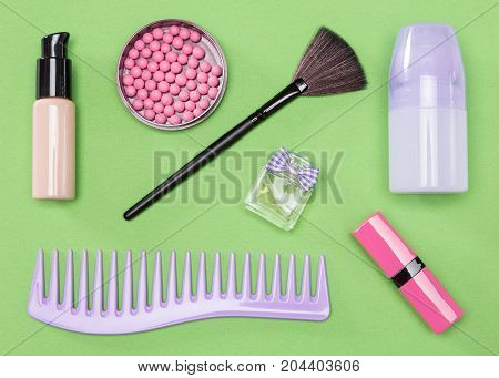 Cosmetic bag essentials: comb, makeup foundation, blush, lipstick, deodorant, perfume, make up brush