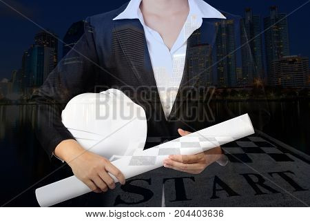 Double exposure of businesswomen in a suit with safety helmet and engineering drawing on night city background, industrial concept.
