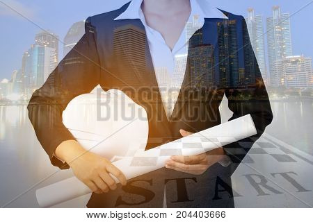 Double exposure of architecture in a suit with safety helmet and engineering drawing on night city background, industrial concept.