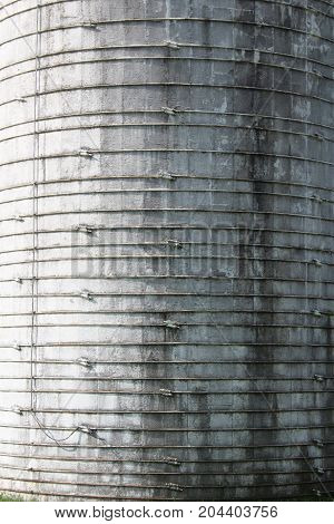 Heavily textured background of a grey concrete silo with metal straps,