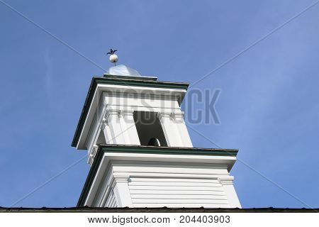 Silver domed bell tower cupola in white trimmed in green,