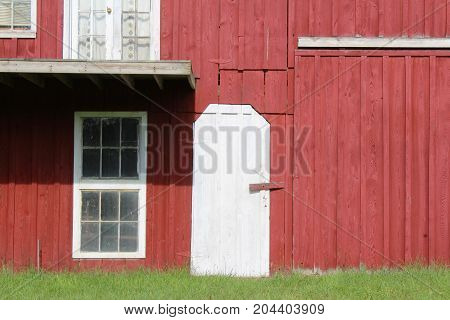 Red painted barn with white door and window trim