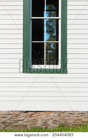 Front view of a window in a white painted clapboard church building trimmed in green, vertical aspect