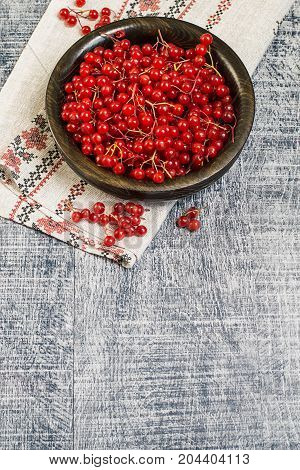 Ripe red berries of a viburnum in a round wooden bowl on an embroidered napkin on an old wooden table. The source of natural vitamins. Used in folk medicine.