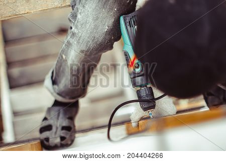 worker tightening the screws with a screwdriver on the front of the building