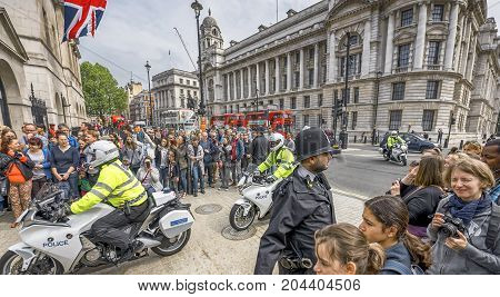 London, May 2016: police cortège and tourists at the entrance to Whitehall