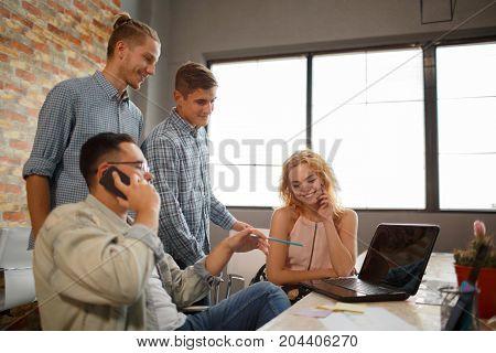 Designers working together at desks in modern office. Start up.