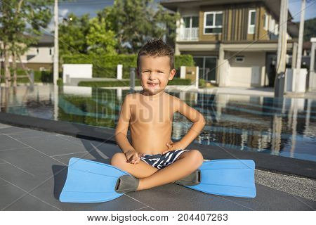 Little boy in a flippers for diving on pool background